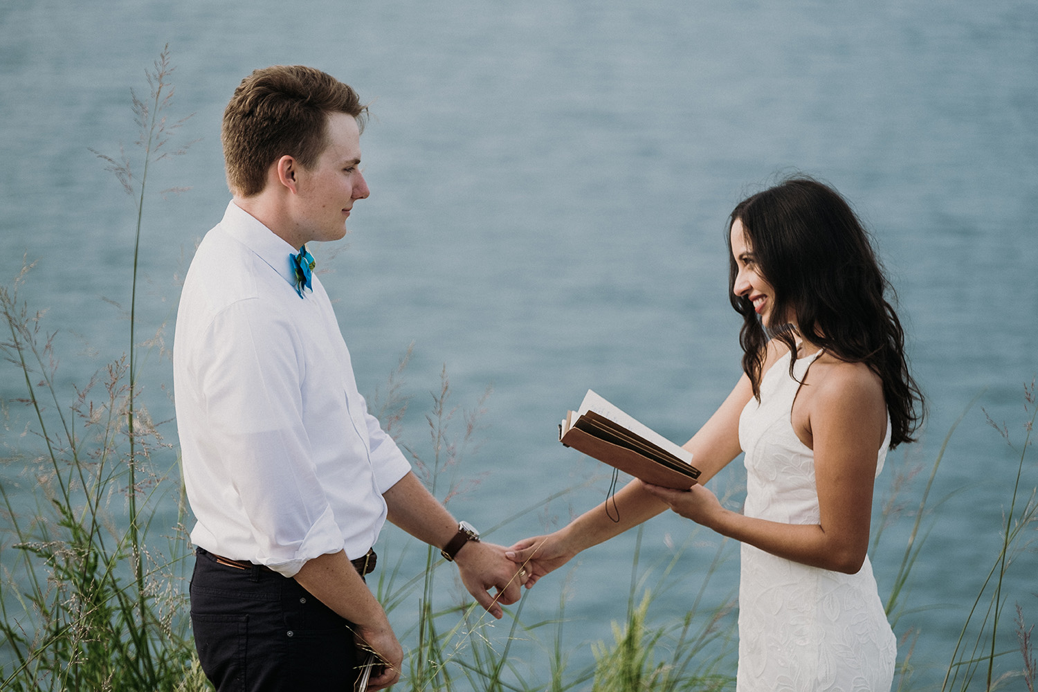 Couple holding hands while reading vows during sleeping bear elopement session