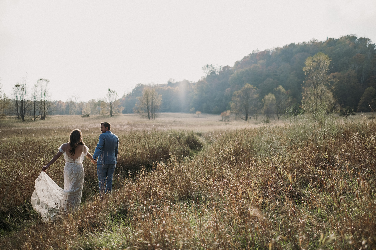 Groom leads Bride through trail during at Sleeping Bear Dunes Elopement Session