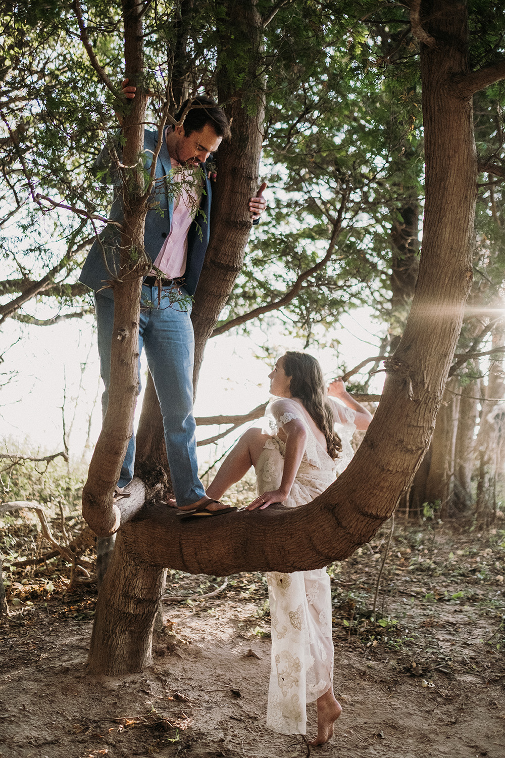 Adventurous couple climbs tree during sleeping bear dunes elopement session with Josh Hartma