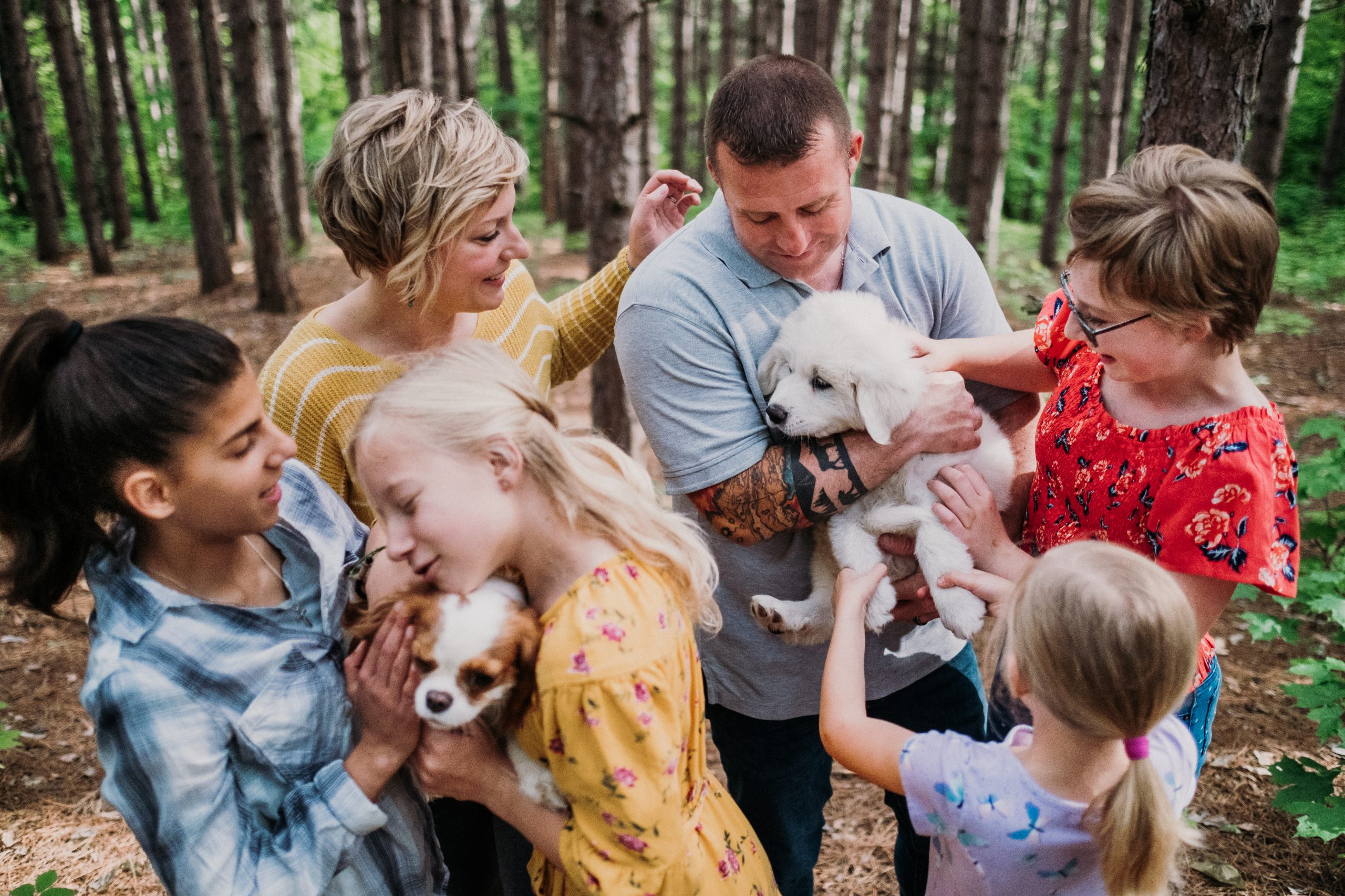 family holding and cuddling with puppies during a family adventure session