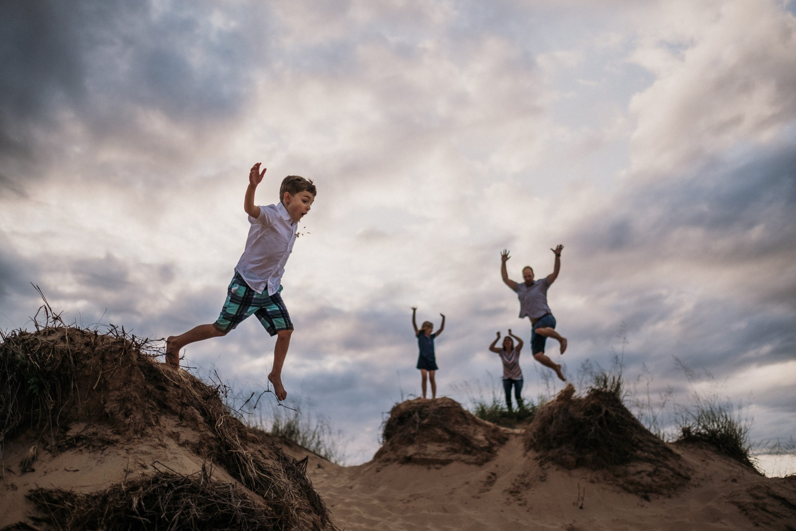 kids leaping of sleeping bear dunes at family adventure session